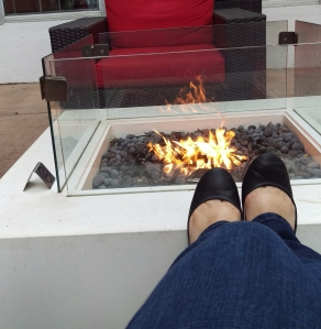 Image of feet propped on edge of enclosed fire pit