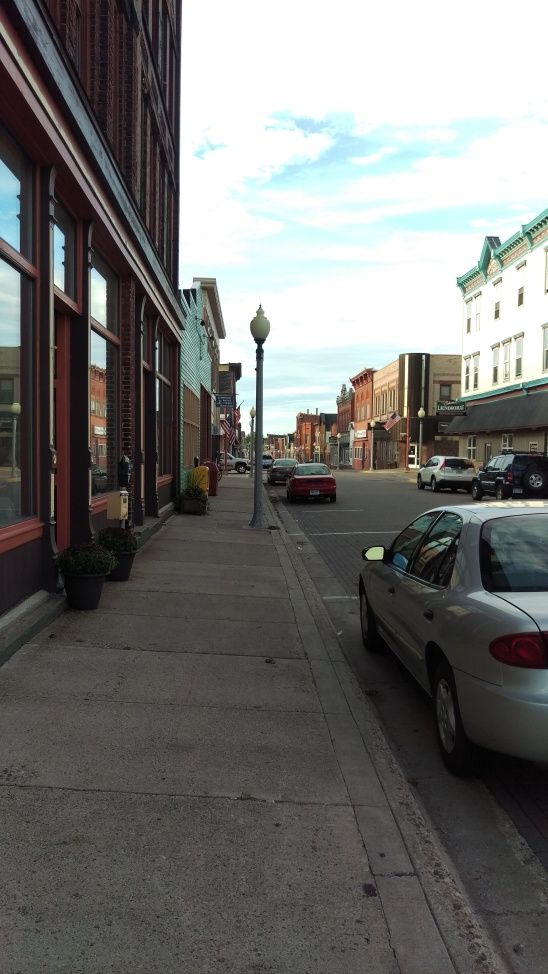 Commercial street with wide sidewalks and store fronts, but no people